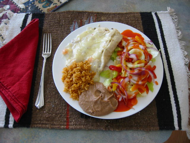 Seafood enchiladas with rice, beans and salad